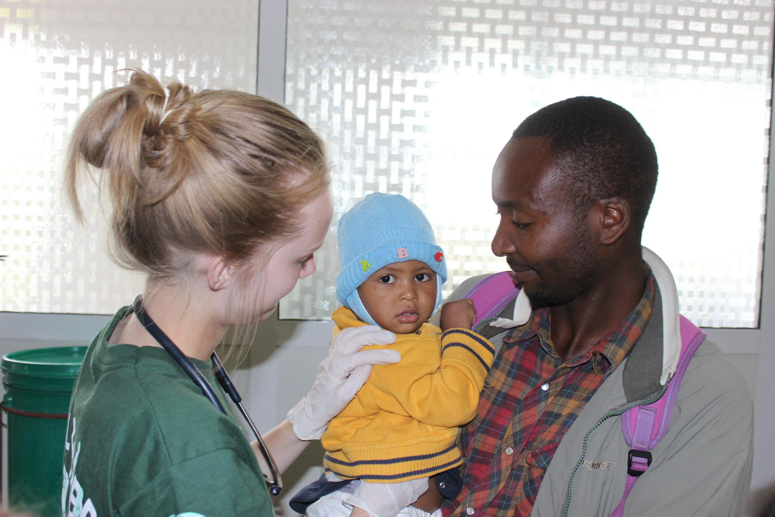 Projects Abroad intern checking a baby's heart beat during her midwifery internship in Tanzania.